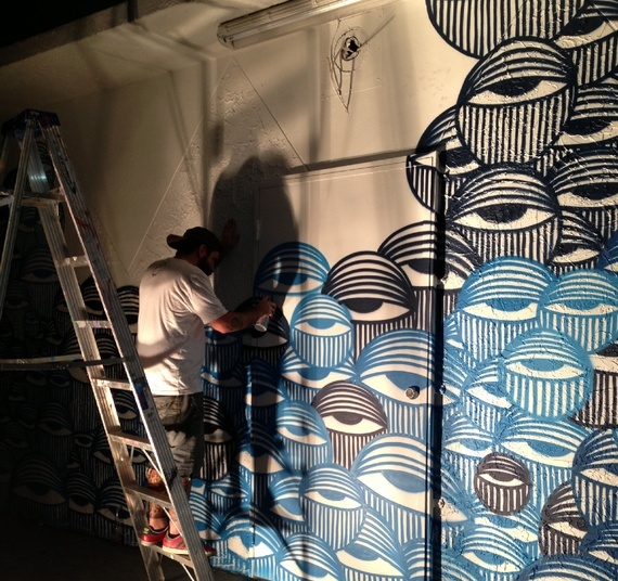 """In Miami's Wynwood Arts District, David Anasagasti works on his """"Ocean Grown"""" mural, a mural at the center of a copyright infringement dispute with American Eagle Outfitters. (via The Atlantic)"""