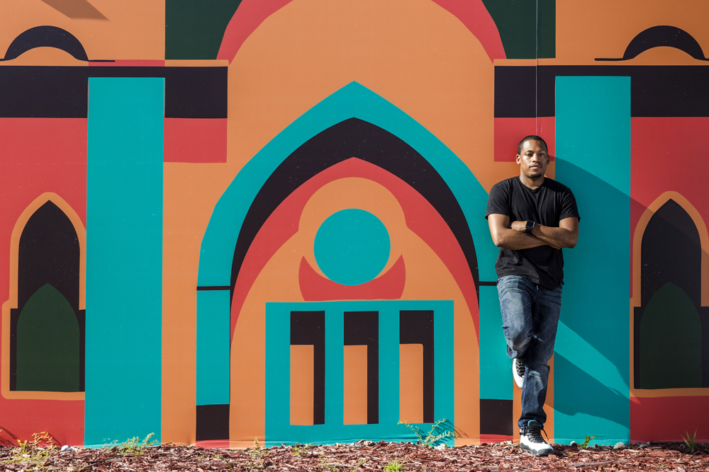 Architect/artist/city planner Germane Barnes in front of the Opa-Locka Community Development Corporation's Arts & Recreation Center. Mural by Lekan Jeyifo. Photo: Matthew Roy, via Curbed.