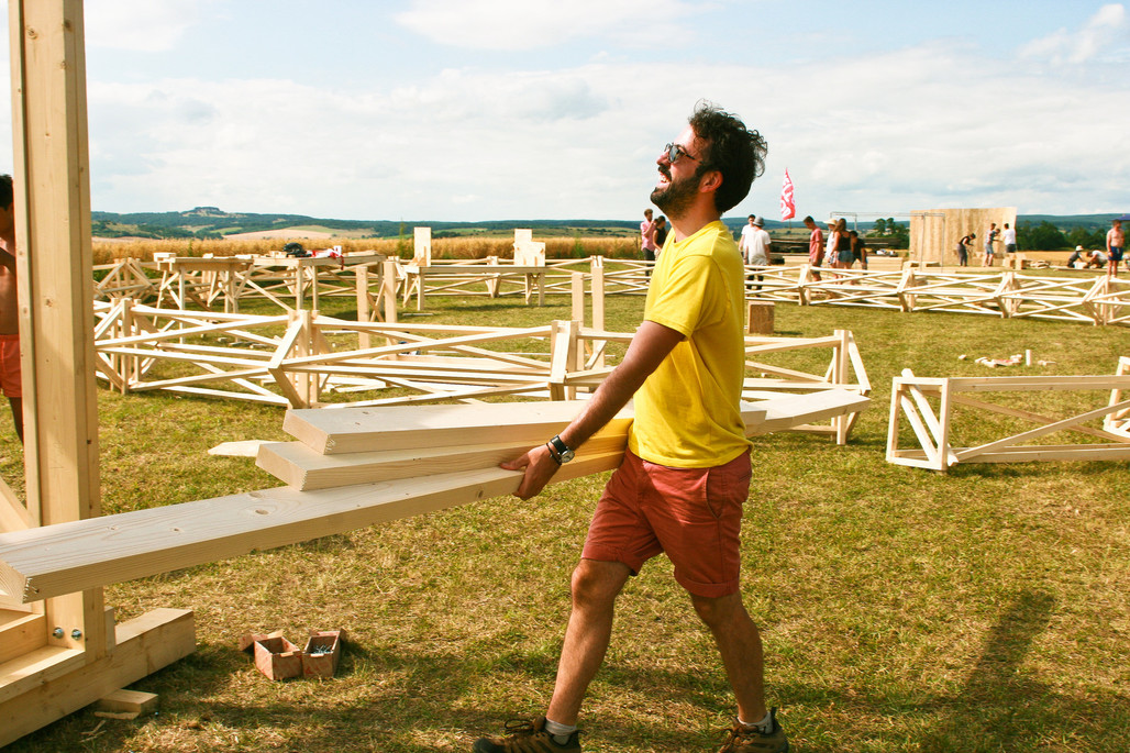 A Hello Wood team member helps build the Project Village (via flickr).