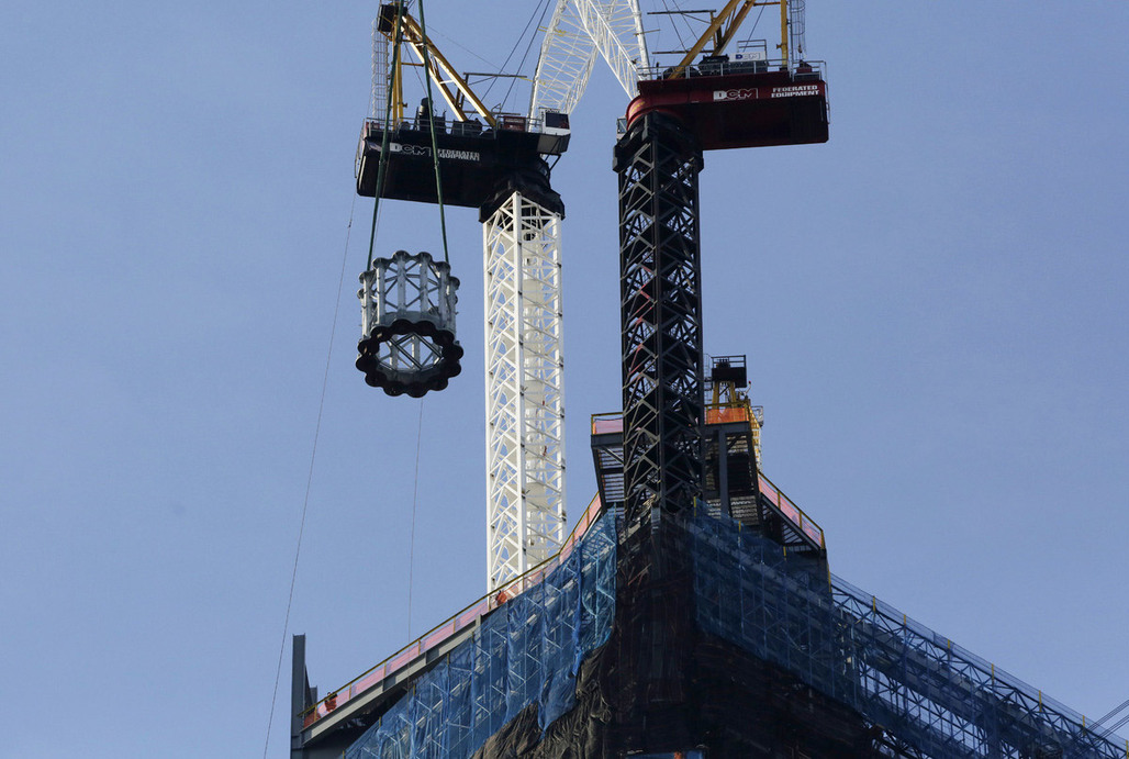 The first section of a 408-foot spire is hoisted by crane to the top of One World Trade Center, Wednesday, Dec. 12, 2012 in New York. The spire will be fully assembled in 2013 and the tower will top out at 1776 feet. (AP Photo/Mark Lennihan)