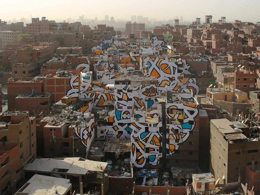 """The piece """"Perception"""" by Tunisian-French artist eL Seed spans over numerous brick buildings in Cairo's neglected Manshiyat Naser neighborhood. (Photo: eL Seed; Image via techinsider.io)"""
