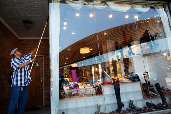 George Aiken, 55, washes the windows of a store on Flatbush Avenue. Credit- Victor J. Blue for The New York Times