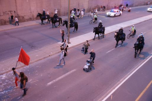A protester carrying a red flag is followed by policemen on horseback in Montreal in 2012. Credit: Nicholas Korody