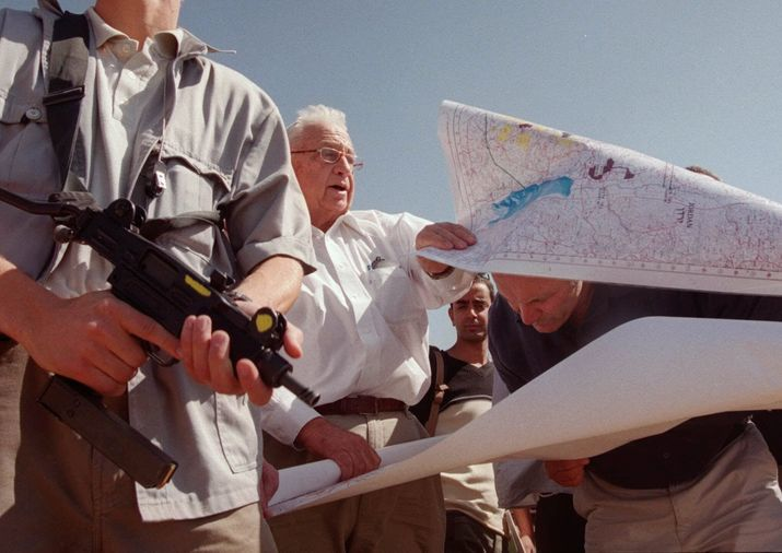 In this Thursday, Oct. 14, 1999 file photo, Ariel Sharon, center, leader of the opposition Likud party, unfurls maps of Israeli settlements in the West Bank with right-wing Knesset member Hanan Porat (AP Photo/Jacqueline Larma, File)