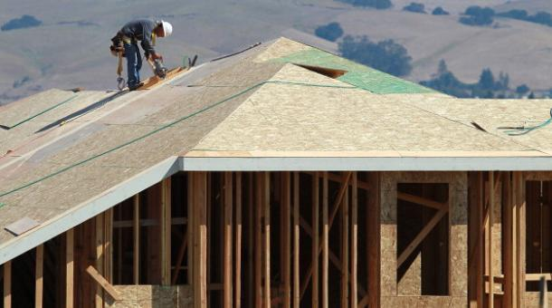 A construction worker cuts a piece of wood on the top of a home under construction at a new housing development in Petaluma, Calif. (Justin Sullivan/Getty Images via marketplace.org)