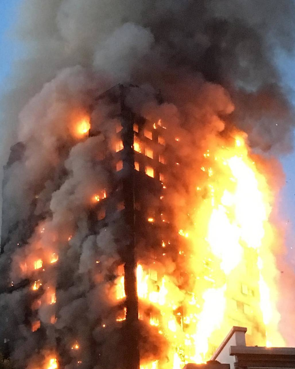 "The 24-story Grenfell Tower completely engulfed in flames as the sun rises over London on Wednesday morning. Image via <a href=""https://www.instagram.com/mrgeorgeclarke/"">@mrgeorgeclarke</a> on Instagram."