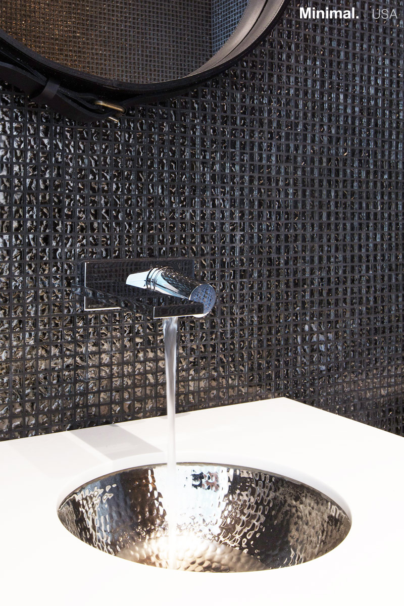 The integrated sink, surrounded by the Corian top, takes up the theme of the mosaic on the wall, keeping the design fluid.