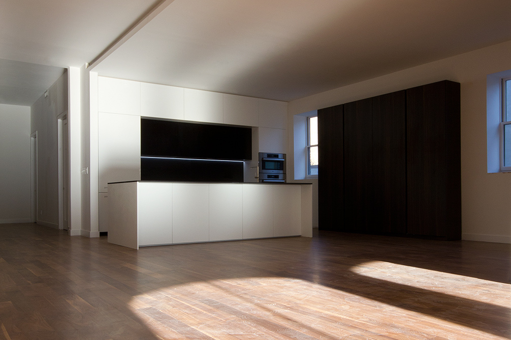 In the open space on the sixth floor, the minimalist design of the island in smooth matte gray Lacquer and CaesarStone quartz countertop, makes the island the focal point of the room.