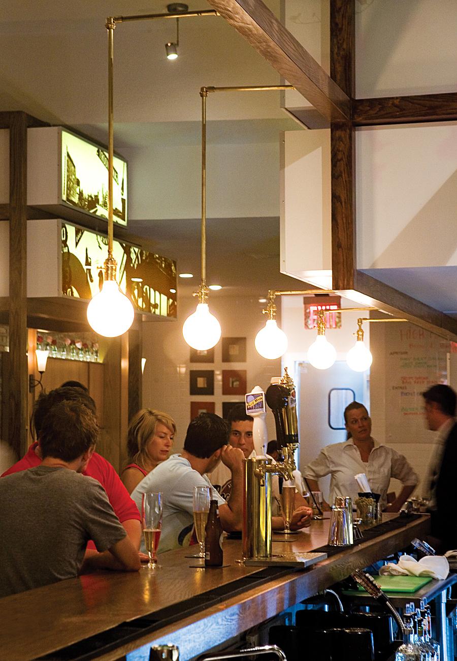 Brass fixtures complement the softness of the classic oak bar counter.