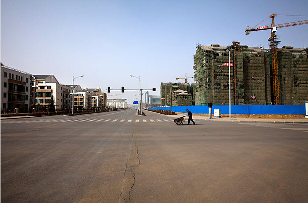 An old man pushes a cart across a road segregating finished apartments and apartments still under construction photo by MICHAEL CHRISTOPHER BROWN FOR TIME