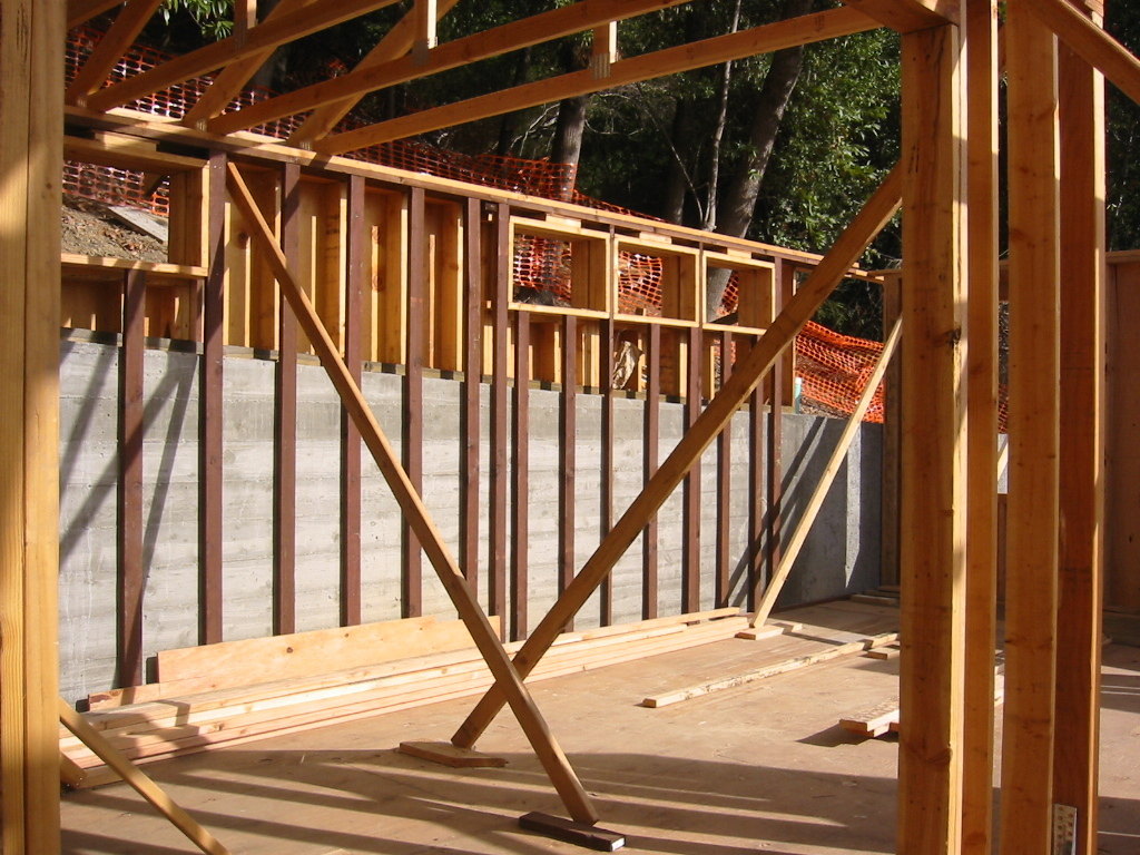 Stick framing with furring at uphill retaining wall.
