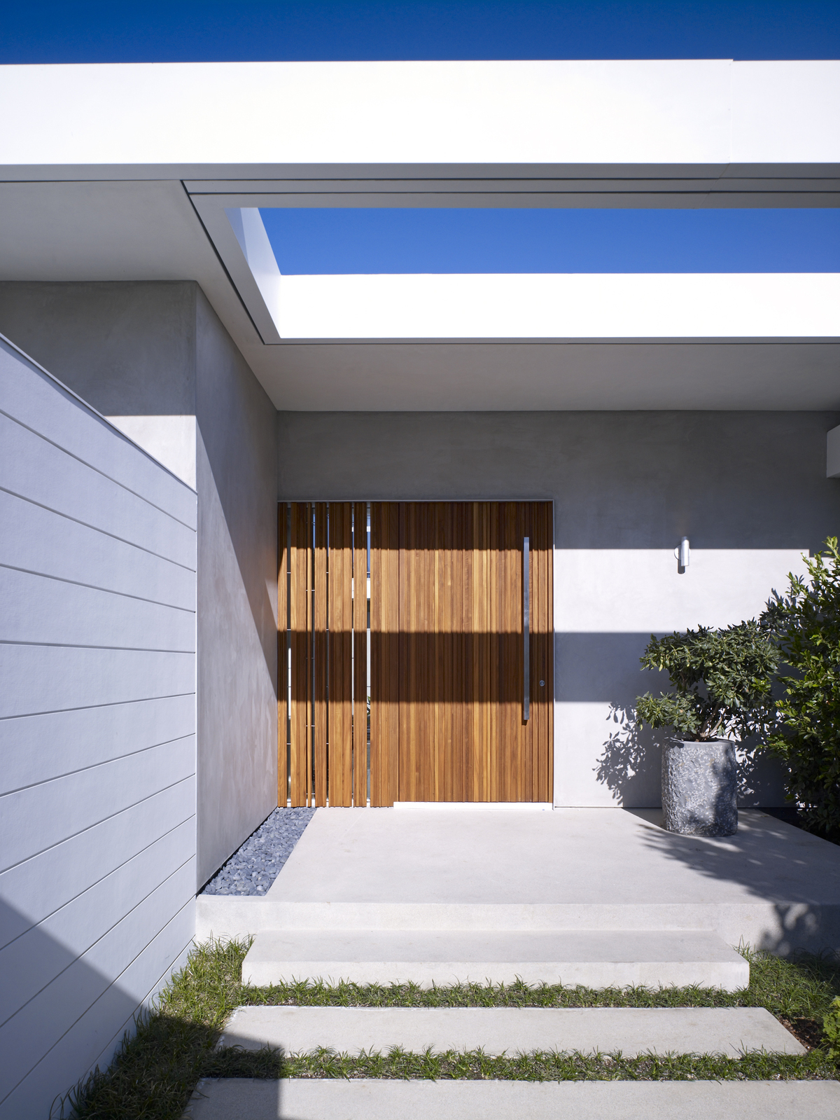An open-air skylight and custom teak entry door