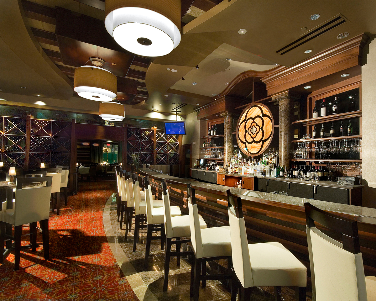 Main bar featuring custom millwork, inlayed mother of pearl backbar focal point, and custom pendant lights.