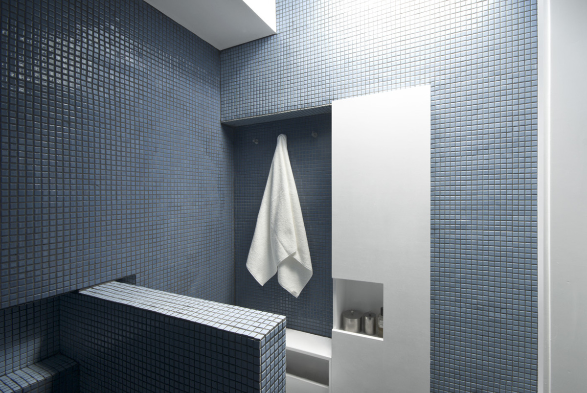 The bathroom, capped by a skylight, is a luminous blue gem