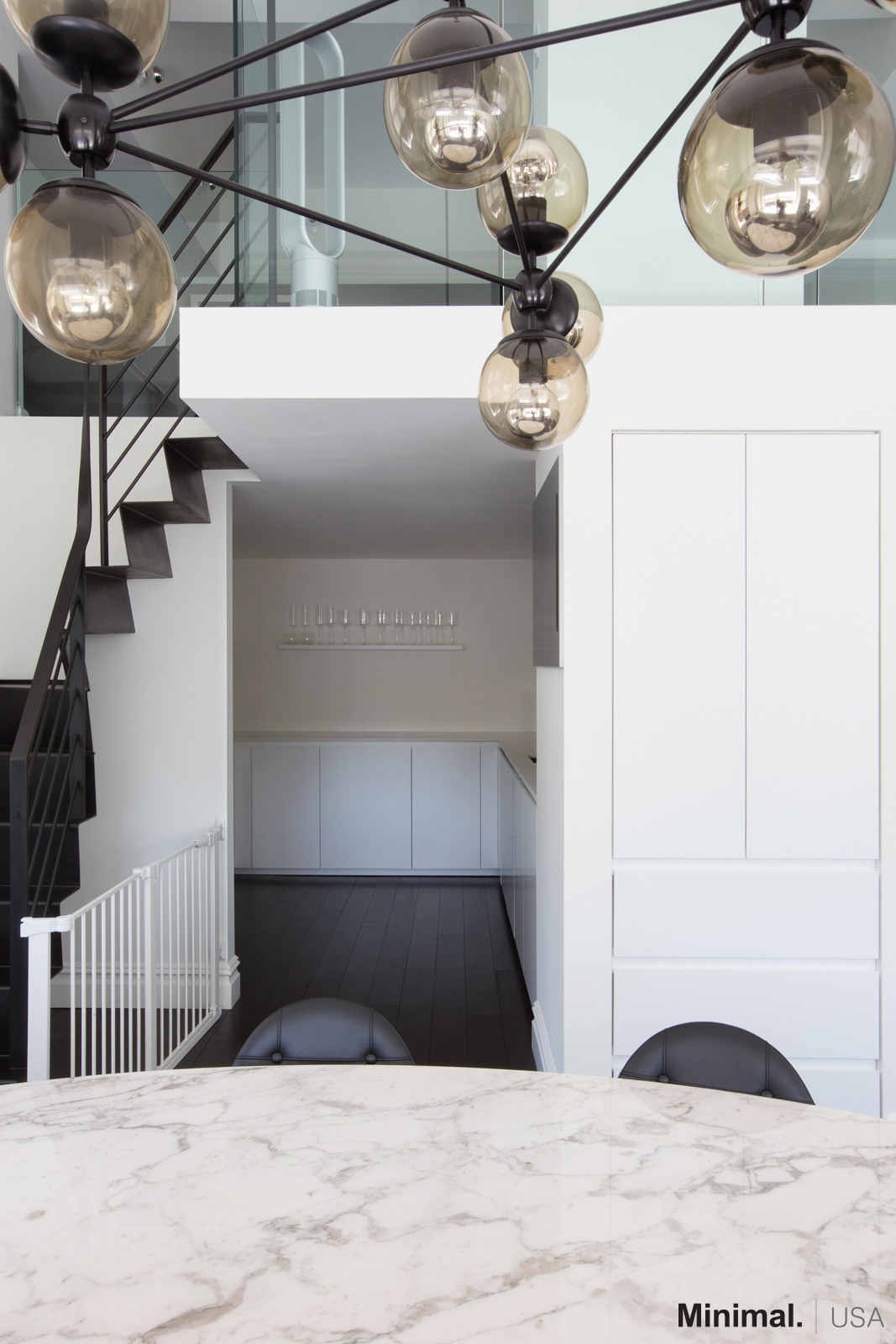 Moving to the left, passing the modern living room, there is the kitchen's entrance with an adjacent pantry cleverly embedded in the wall, becoming an integral part of the column.