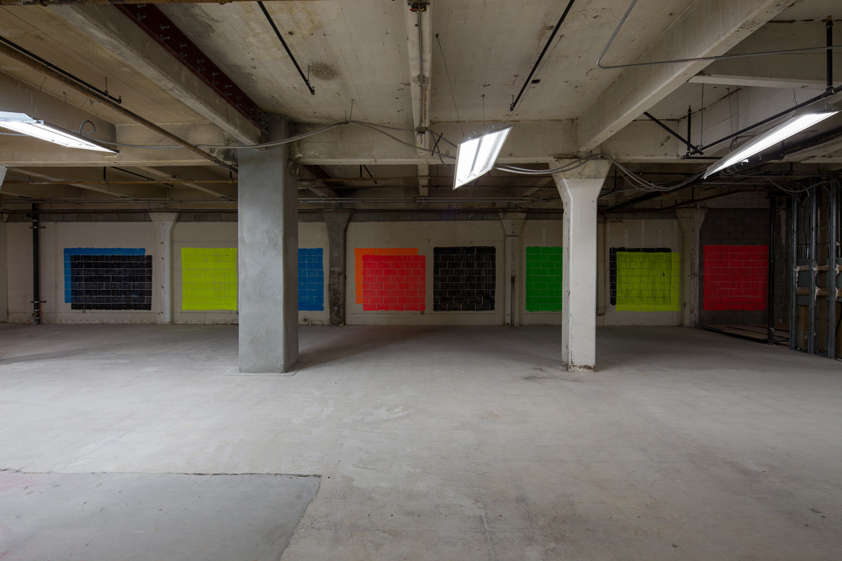 On one side of the space, Nesbit suspended large concrete panels. On the other, he swiped directly on the brick walls. Credit: Taiyo Watanabe