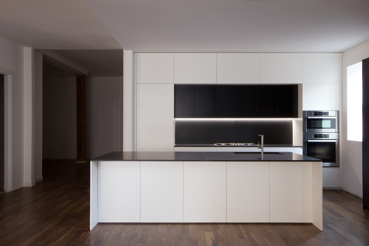 Enhancing the sculptural design of the kitchen, is a strip of LED lights just below the one and only line of open shelving against the wall.
