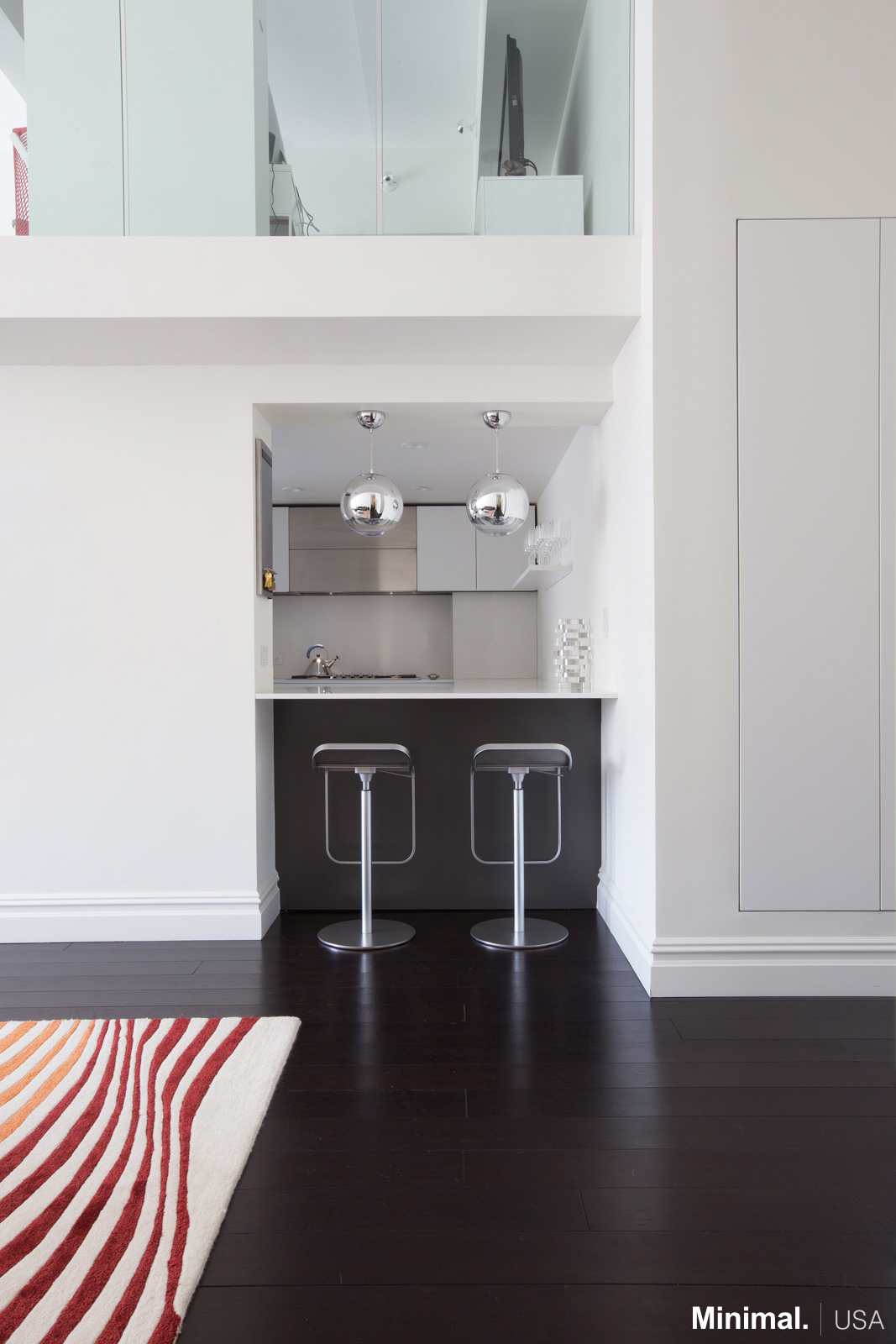 Entering the apartment, the attention is caught by the open space between the two walls that surround the area of the kitchen, used as a bar that lets to glimpse the stylish kitchen.