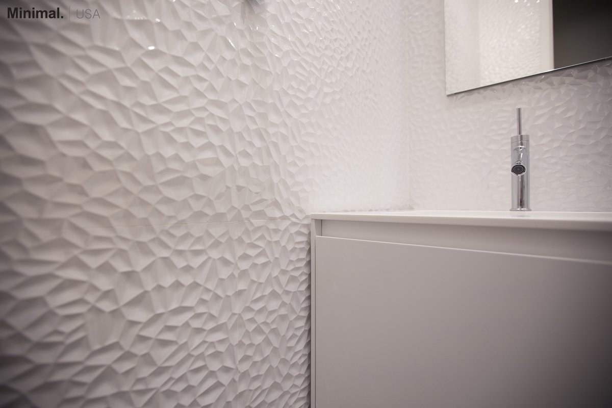 The cube vanity integrates in this bathroom a square sink, carved directly from the top made of Corian. Minimal USA has provided the fixtures also for the tub/shower.