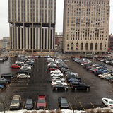 Current situation of Flint's central downtown parking lot: Mott Foundation building is on the right; Genesee Towers, on the left, is slated for demolition (Image courtesy of Flat Lot Competition)