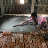A member of the community lending a hand and smoothing his new concrete floor. Image courtesy of ARCHIVE.