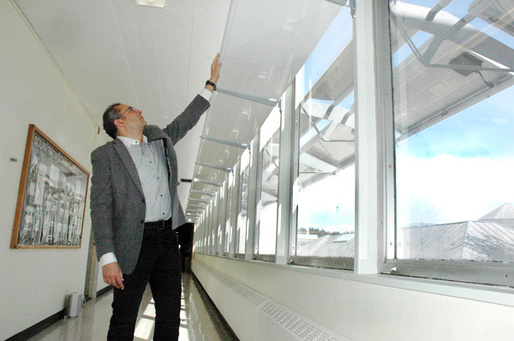 Above: Associate Professor Ihab Elzeyadi examines the SolarAwning™ 3-in-1 system showing indoor LED luminaire, Daylighting Reflector, and PV Shade. Photo by Gregg Kleiner.